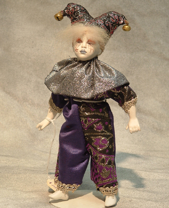 Part of the Uta Brauser's Renaissance Figurines, this small boy is dressed in a purple and silver brocade outfit and jester's hat. $295.00